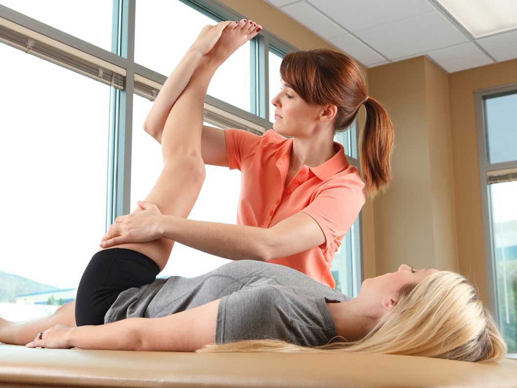Female physical therapy assistant helps a patient with leg exercises.