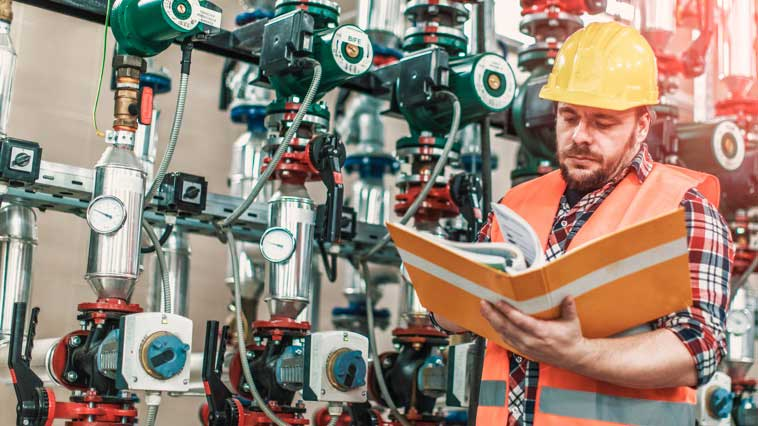 Male pipefitter analyzes a blueprint to determine what the next step on the job is.