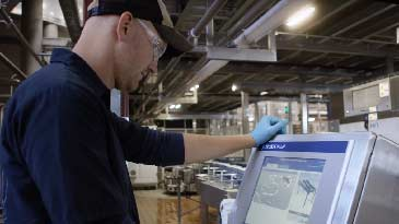 An industrial engineering technician looking at a screen on a machine on the shop floor.
