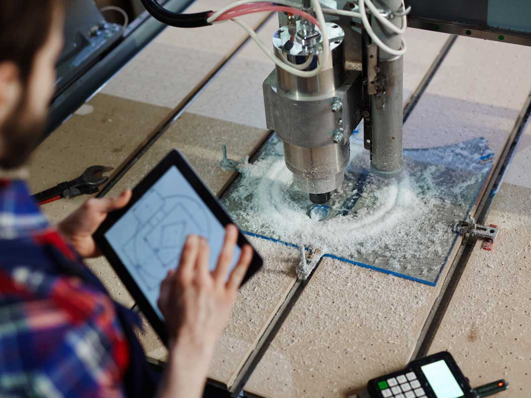 Industrial engineering technician interpreting schematic diagrams on a tablet.