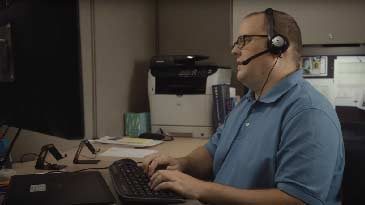 A computer user support specialist working on his computer while talking on his headset with a client.