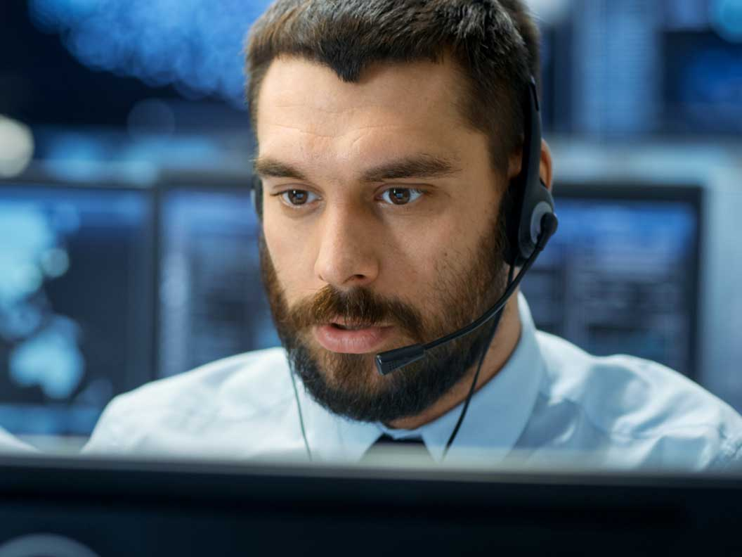Male computer user support specialist on headset diagnosing a customer's computer problem.