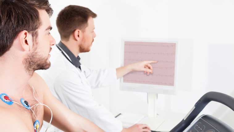 Male cardiovascular technician explains exercise stress test procedure to a male patient.