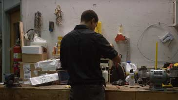A male electrician working on some electrical wires on a work bench.