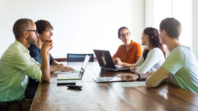 Web developers meeting with clients to discuss the needs and design of a website.