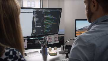 A web developer showing another web developer code on a computer screen.