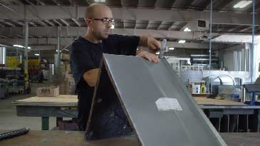A sheet metal worker working on a piece of metal.