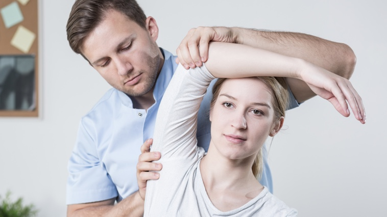 Male massage therapist assists a female patient with stretching exercises.