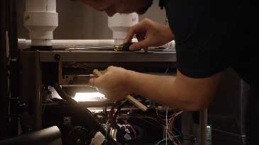 An HVAC mechanic working on a furnace.
