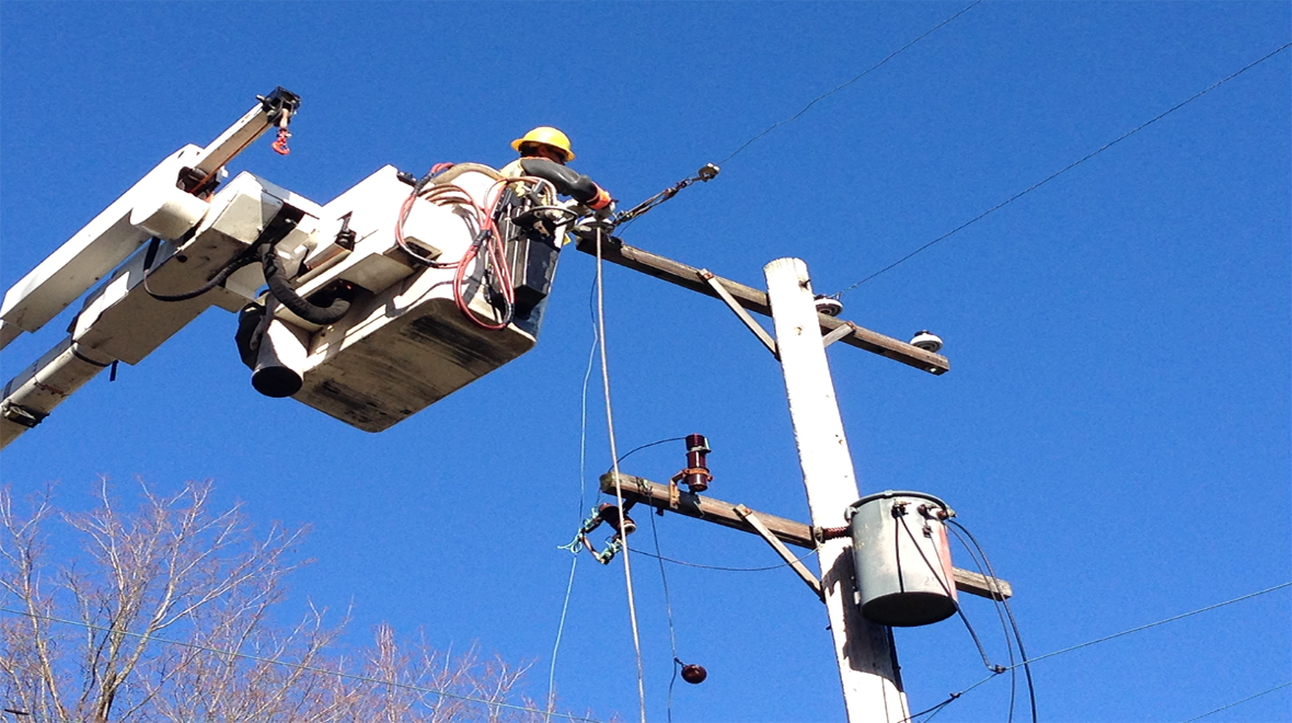 A Consumer Energy Lineman working in a bucket truck.