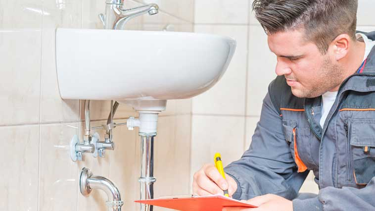 Male plumber inspects a bathroom faucet to prepare a cost estimate.