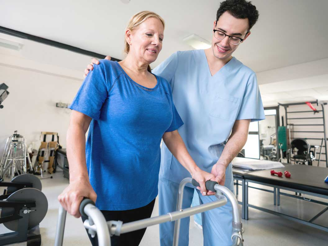 Male physical therapy assisstant helps a female patient with her walker.