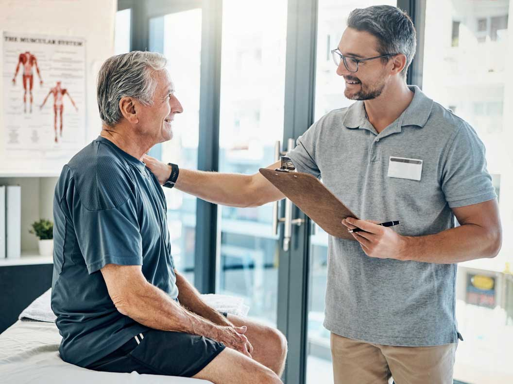 Male PT assisstant talks to male patient about what to do after treatment.