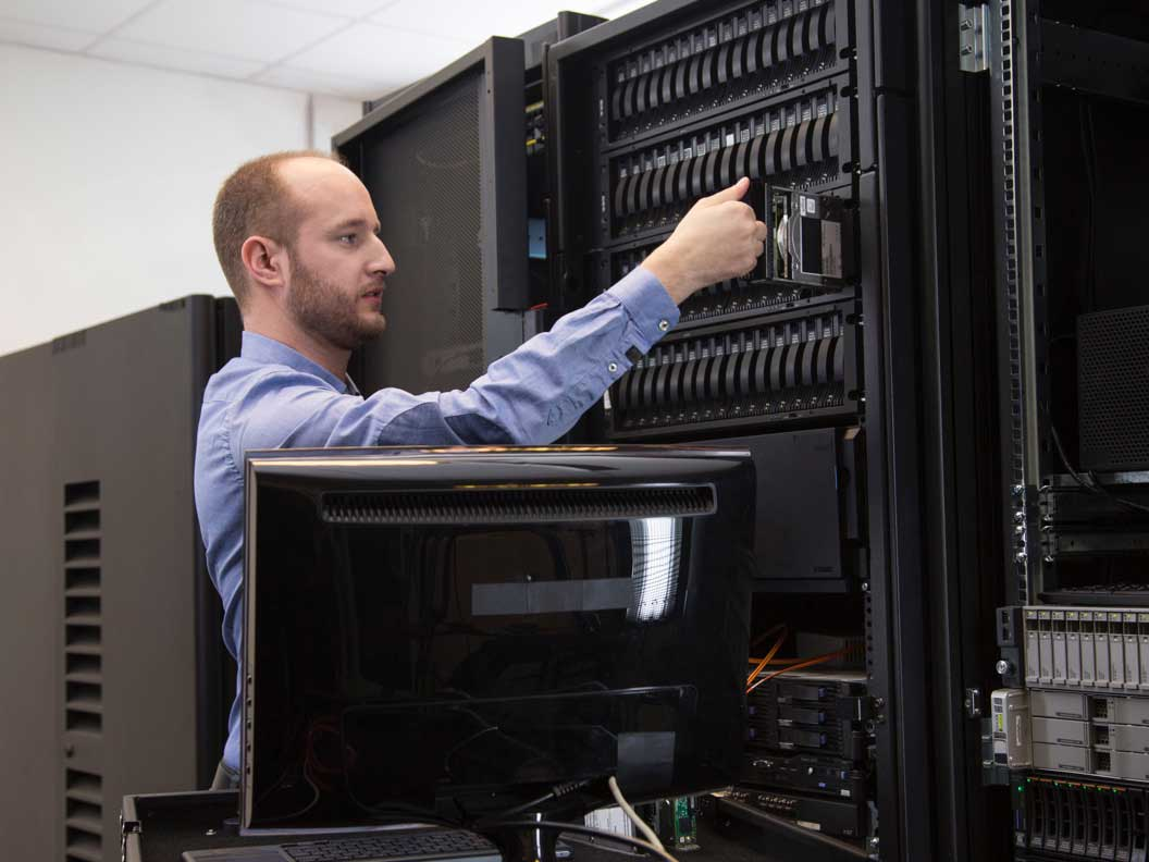 Male computer network support specialist performing maintenance on a large network server.