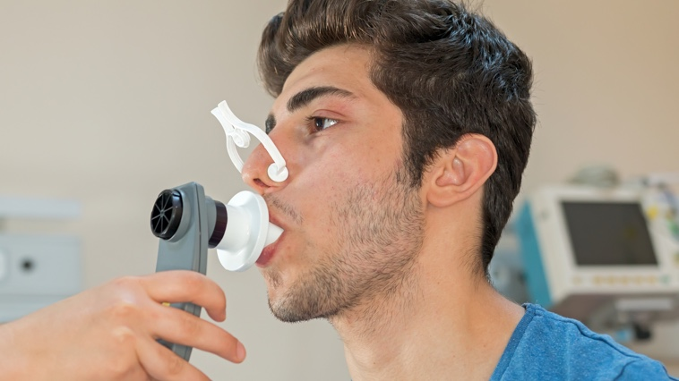 Male respiratory therapy patient taking pulmonary function test.
