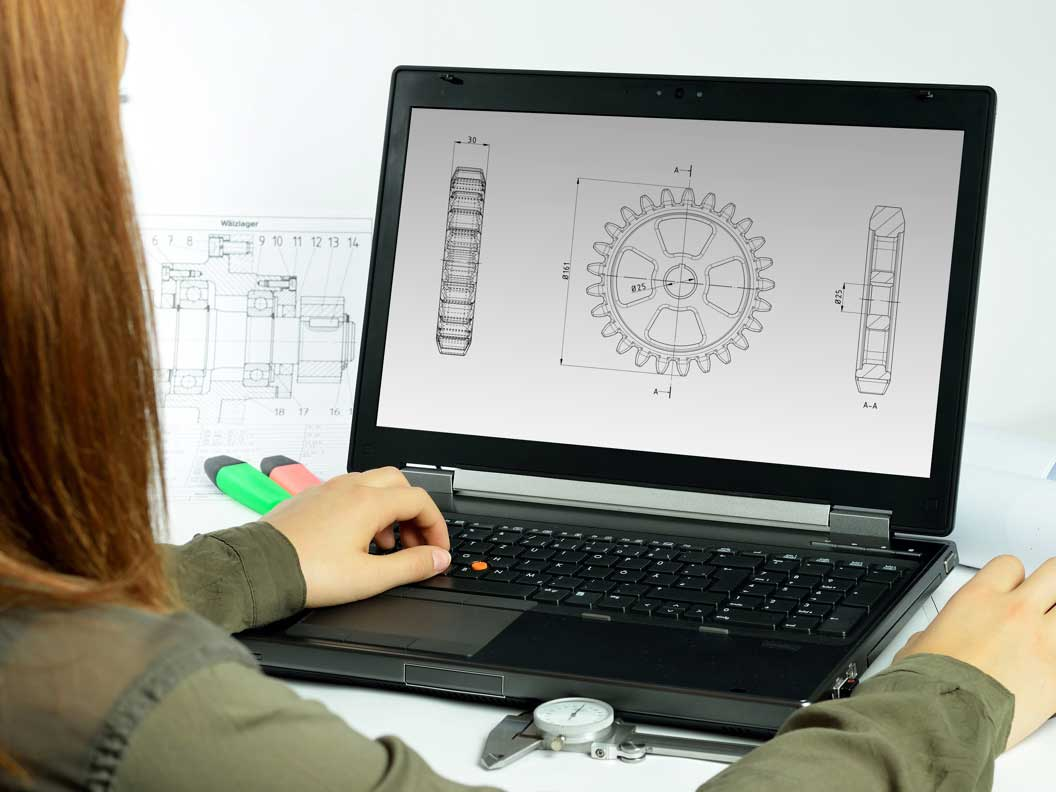 Female mechanical engineering technician using software to prepare layouts of parts to be made.