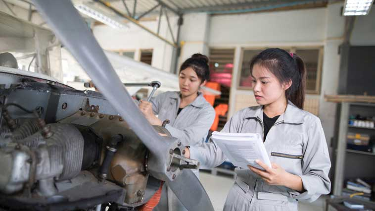 Female engineering technicians inspect products for flaws.