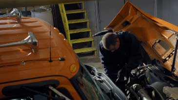 A bus and truck mechanic working on his diesel truck.
