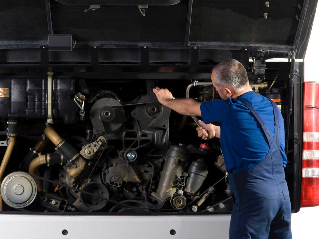 Male bus and truck mechanic performing an under the hood check.