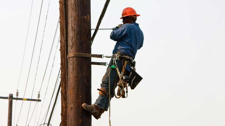 Male power-line repairer works on repairing electrical power-line pole.