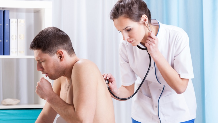 Female respiratory therapist uses a stethoscope to listen to a male patient's lungs.